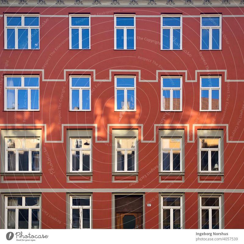 Rote Hausfassade mit Mustern um die Fenster urban Außenseite Glas geometrisch Gebäude Architektur Reihen Design architektonisch im Freien Struktur außerhalb
