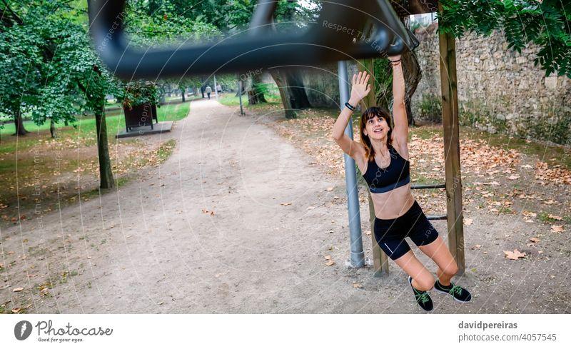 Frau macht Affenübungen auf Ringen Athlet Sportlerin Training Affenstangen Ringübung Park Übung für Affen jung stark erhängen Menschen passen Gesundheit Körper