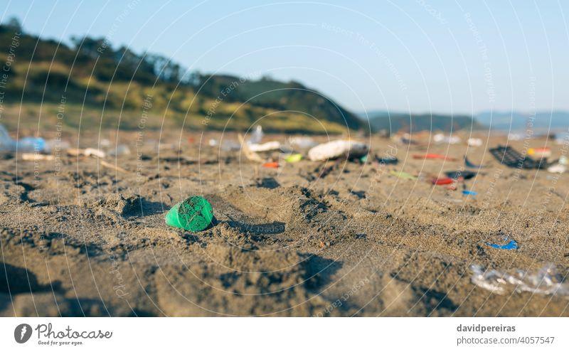 Schmutzige Strandlandschaft voller Müll Kunststoff Sand dreckig kontaminiert Umwelt Natur Verschmutzung Abfall Küste Kunststoffdeckel Problematik