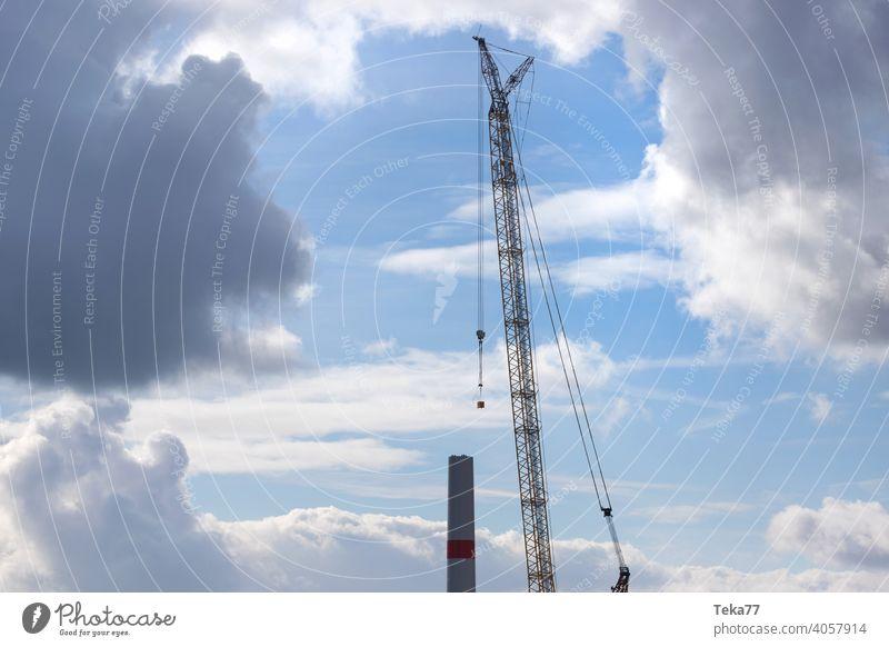 eine moderne Windkraftanlagen-Baustelle Windkraftanlagenbau Baukran Schwerlastkran Windrad Abend Ökostrom Winter Blauer Himmel gelb schwer Farben im Freien