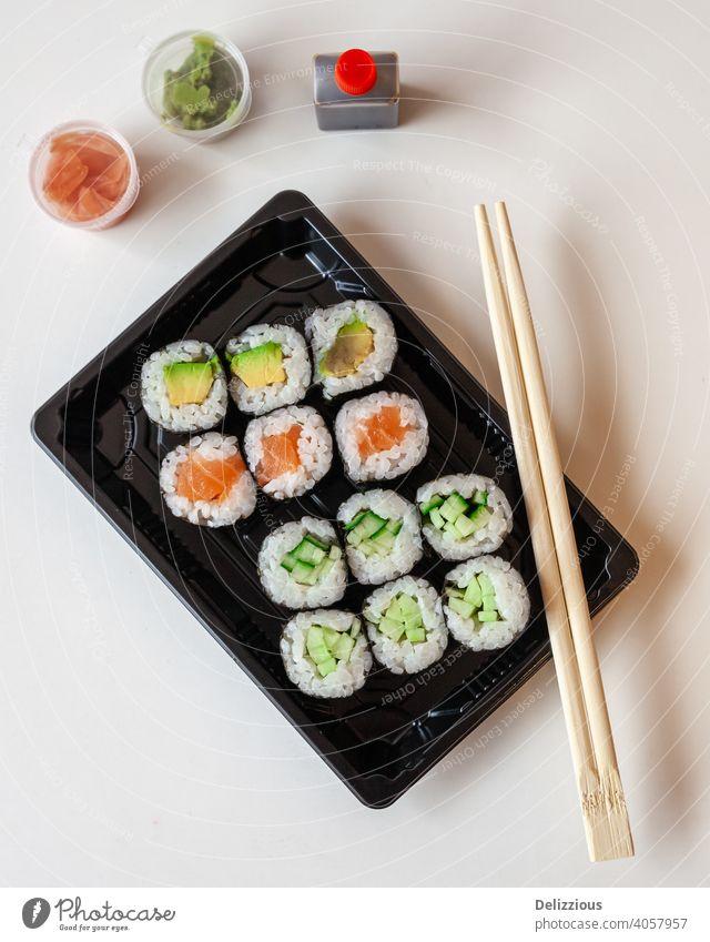 Ansicht von oben auf frisches Sushi zum Mitnehmen auf weißem Hintergrund mit Kopierbereich sushis Stäbchen Lebensmittel Ingwer Wasabi Japanisch