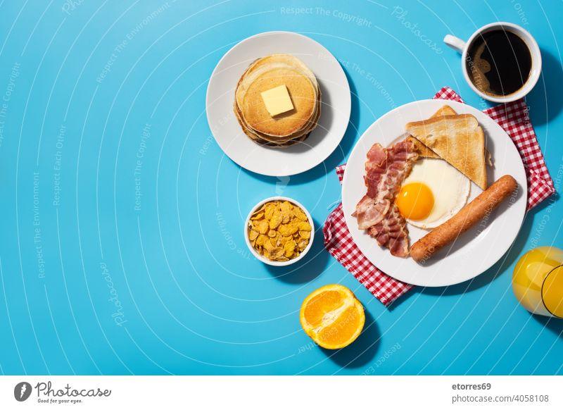 Traditionelles amerikanisches Frühstück auf blauem Hintergrund amrican Speck Brot Butter Zerealien Speise Ei Fett Lebensmittel gebraten Frucht Saft Ernährung