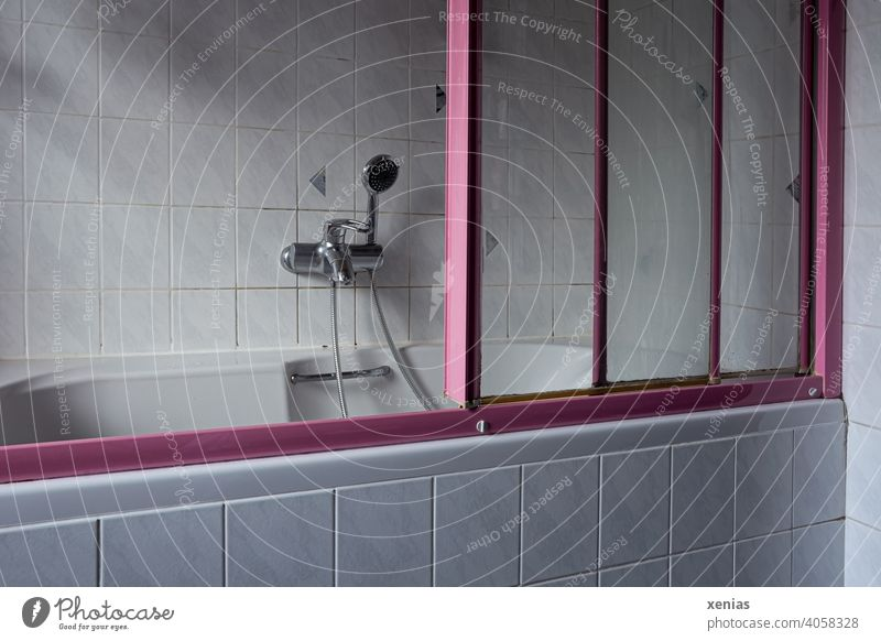 Im alten Badezimmer steht eine seniorenungeeignete alte Badewanne mit rosa Schiebetüren, Handbrause, Handgriff und hellen Fliesen baden duschen