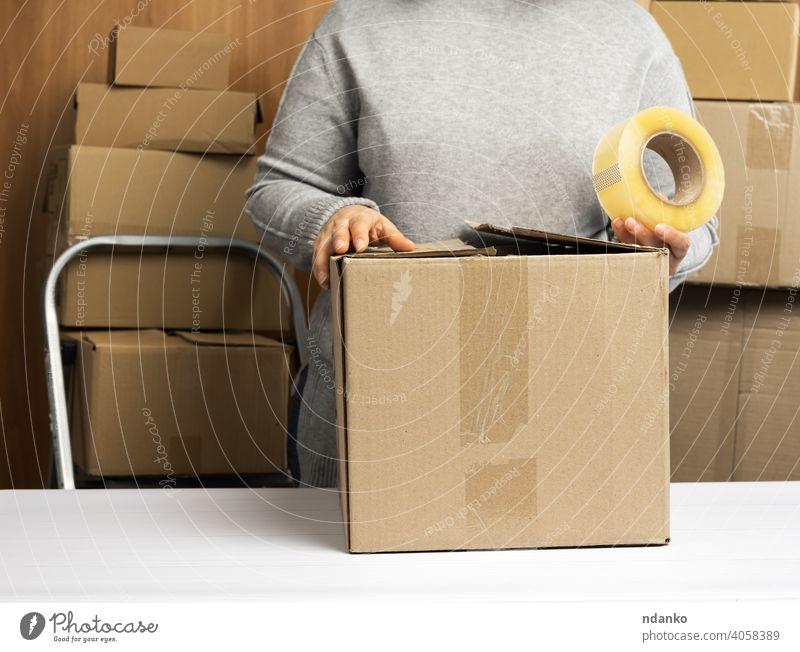 Frau im grauen Pullover hält eine Rolle Klebeband und packt braune Kartons auf einem weißen Tisch, hinter einem Stapel von Kartons Lifestyle wirklich viele