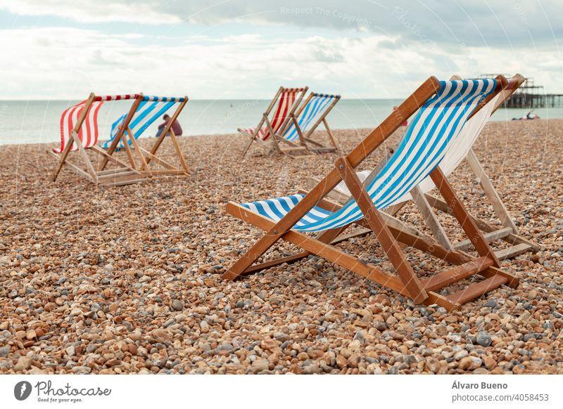 Leere rot und blau gestreifte Liegestühle in Brigthon, Großbritannien. Hängematten Stühle Miete Strand weiß MEER Material Holz Ärmelkanal Atlantik Südengland