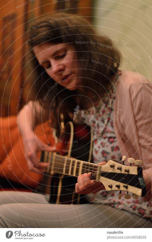 versunken ins Gitarrenspiel - junge brünette Frau sitzt zuhause auf dem Sofa und spielt Gitarre Musik Musikerin spielen musizieren Kunst Kleinkunst