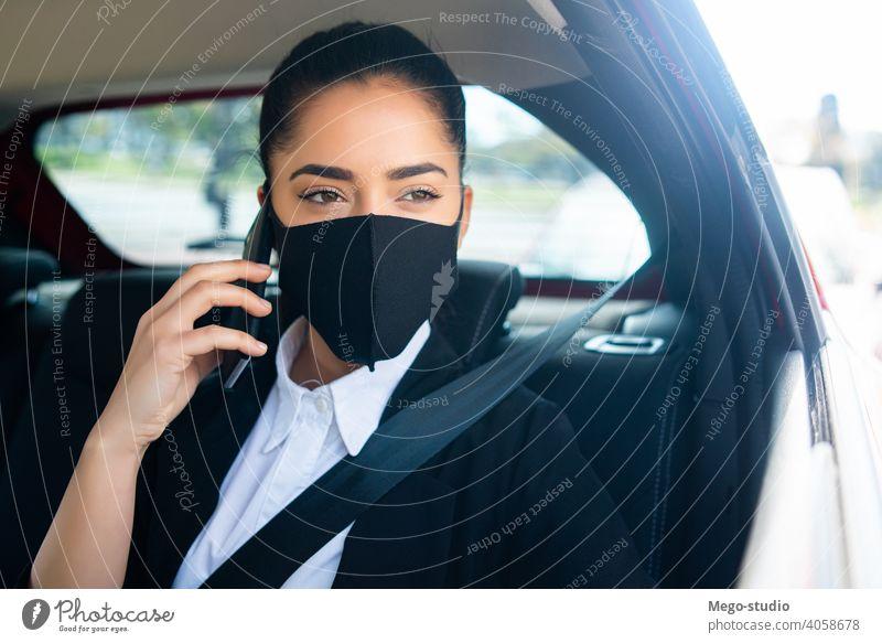 Geschäftsfrau telefoniert im Auto. Frau PKW Mobile Telefon Gesichtsmaske Mundschutz covid-19 reden sprechend Taxi Transport Kabine eine Porträt Erwachsener