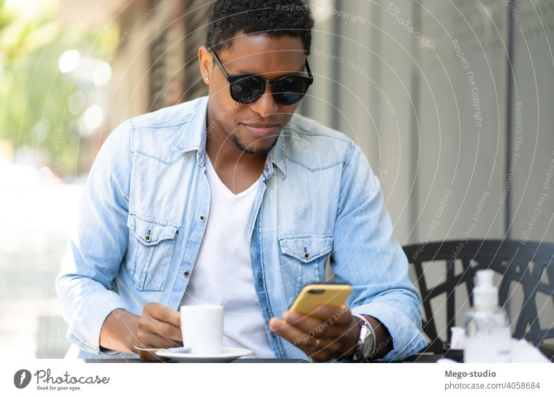 Mann benutzt sein Mobiltelefon in einem Café. Mobile Telefon urban Großstadt Afrikanisch Amerikaner Kaffeehaus Technik & Technologie Smartphone sozial Medien