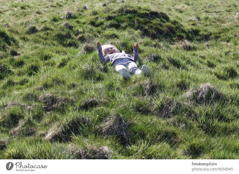 Kind liegt auf einer grünen Graswiese Wiese Kindheit Wachstum Lebensfreude Erholung Naturerlebnis Zufriedenheit Wohlgefühl Gesundheit Vorschulkind