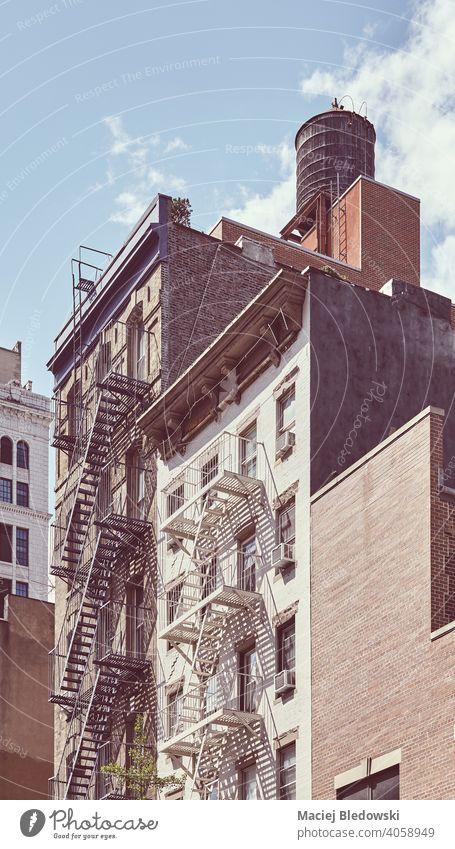 Mietshäuser mit Feuerleiter in Manhattan, farbig getönt, New York City, USA. New York State Großstadt Feuertreppe Gebäude Mietshaus Haus altehrwürdig nyc retro