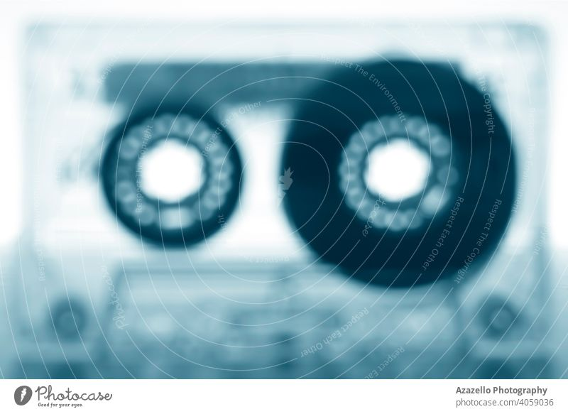 Unscharfes Bild einer Audiokassette in blauem Monochrom 80s 90s abstrakt gealtert analoge Aufzeichnung Audiorekorder Audio-Oldtimer Hintergrund Unschärfe