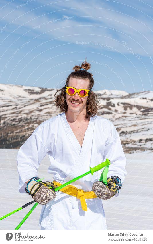 Skifahrer als Karateka verkleidet an einer Skistation Sport Aktion aktiv Aktivität Abenteuer künstlerisch schön kalt cool Tracht bergab extrem Extremskifahrer