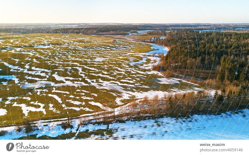Saisonwechsel. März ländliche Landschaft. Winterkulturen und gepflügtes Feld-Panorama. Schnee Frühling Natur Antenne Hintergrund Baum weiß Wald grün Straße