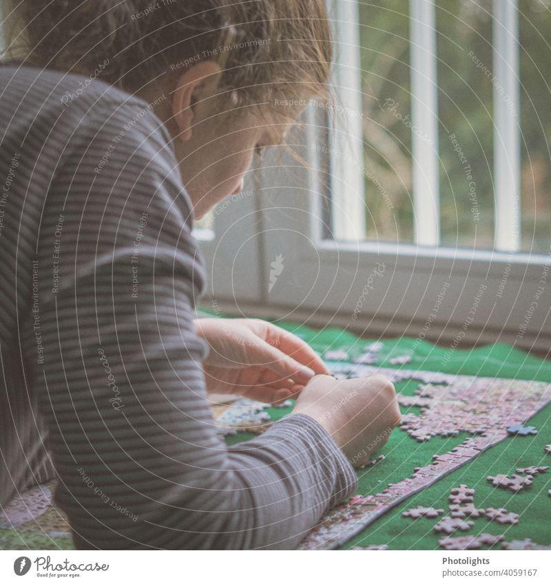 Junge Frau schaut sich ein Puzzleteil an puzzlen Farbfoto Teile u. Stücke Freizeit & Hobby Spielen mehrfarbig Spielzeug Innenaufnahme Suche Problemlösung
