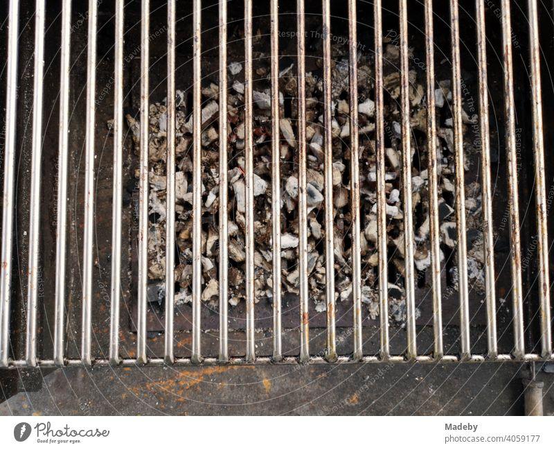 Grillrost über Resten von Holzkohle auf einem rostigen alten Holzkohlegriil bei einem Barbecue in Rudersau bei Rottenbuch im Kreis Weilheim-Schongau in Oberbayern