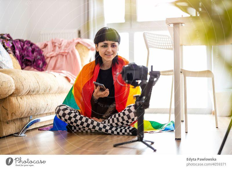 Gender-Fluid-Person in Regenbogenflagge eingewickelt, die einen Vlog mit Kamera filmt lgbtq echte Menschen nicht-binär Vlogger geschlechtsfluid Blogger
