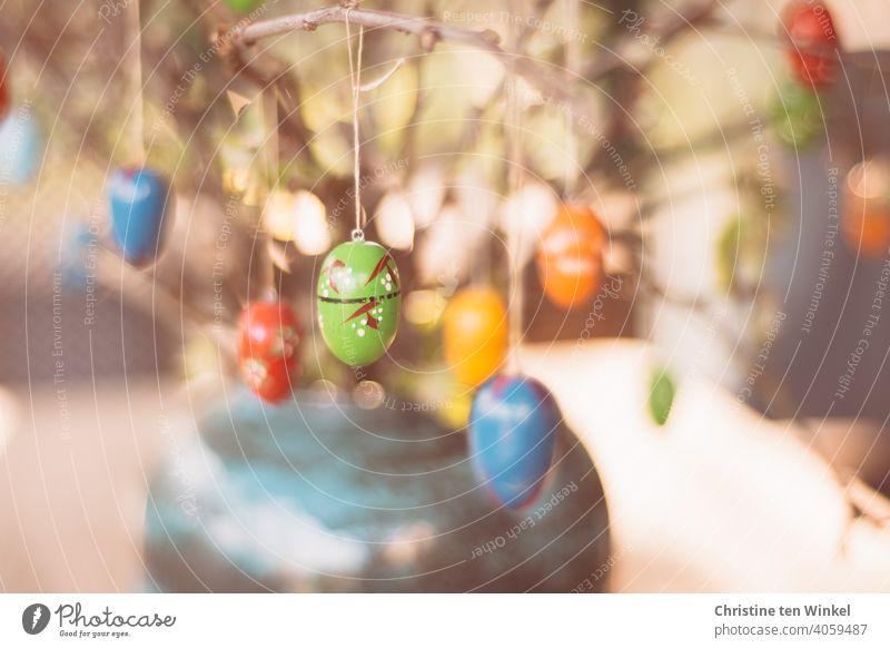 Bunte Ostereier aus Holz hängen an den Zweigen, die als Osterdekoration in einer Vase stehen Ostern osterdekoration Dekoration Osterfest Holzeier bunt