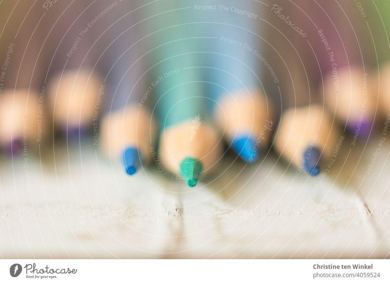 Symmetrisch angeordnet liegen die Buntstifte mit den Spitzen zum Betrachter auf hellem Untergrund bunt gemischt malen zeichnen Stifte Grundschule Kindergarten