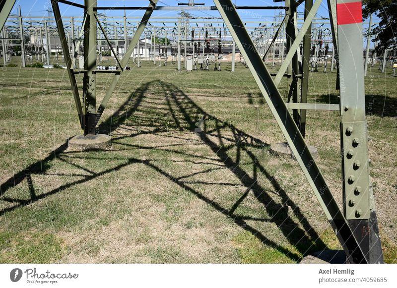 Blick unter einen Hochspannungsmast auf seinen Schatten Energie Energiewirtschaft energiewenge erneuerbare Erneuerbare Energie Kabel Hochspannungsleitung