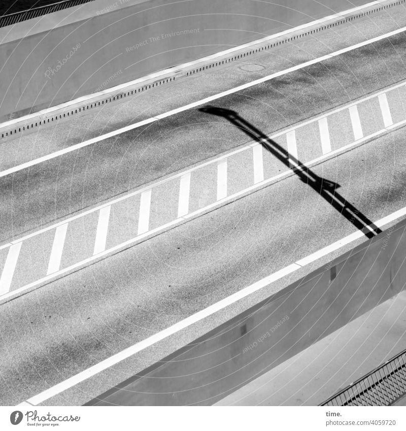 gegenläufig verkehr straße autofrei schatten sonnig spuren linien mittelstreifen Verkehrszeichen grau asphalt straßenbelag vogelperspektive diagonal geländer