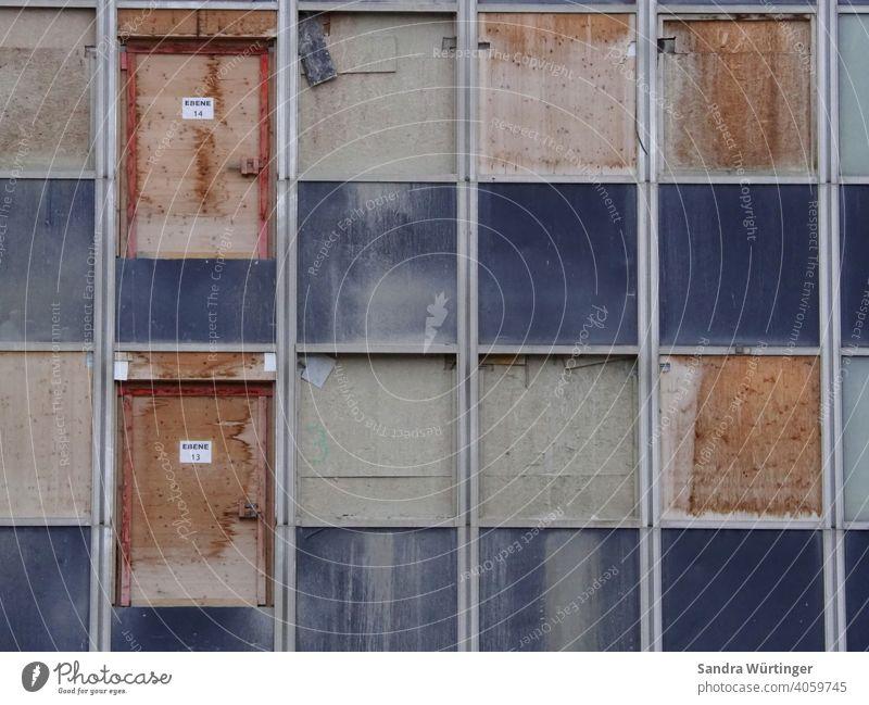 Baustelle eines Hochhauses, mit Holz verschlagene Türen und Fenster Sanierung Gebäude Fassade Haus Architektur Außenaufnahme Hochhausfassade Siemens Holzbrett
