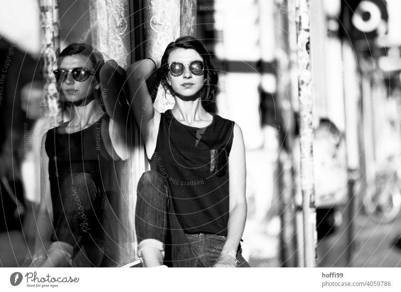 Die junge Frau blickt in die Kamera Junge Frau brünett Porträt Blick in die Kamera hübsch Sonnenbrille 1 Beautyfotografie Schwarzweißfoto natürlich Stadt