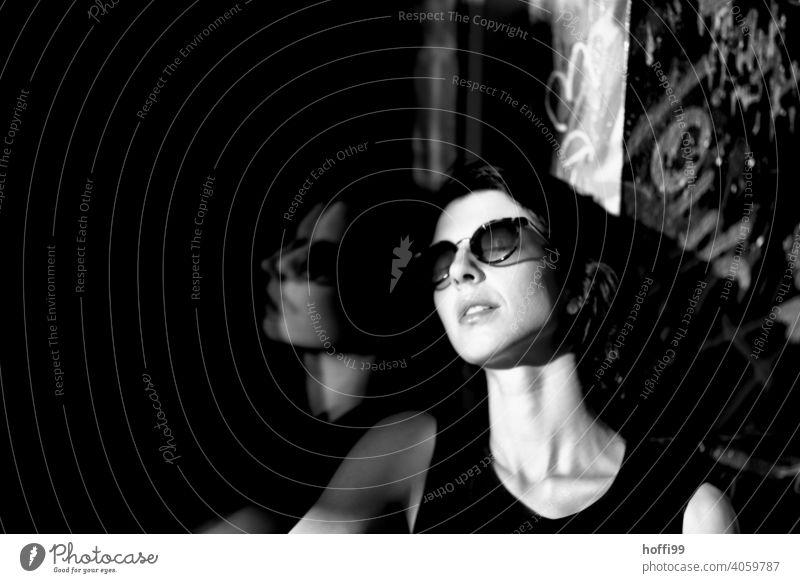 Die junge Frau genießt die Sonne Junge Frau brünett Porträt Blick in die Kamera hübsch Sonnenbrille 1 Beautyfotografie Schwarzweißfoto natürlich Stadt Viertel