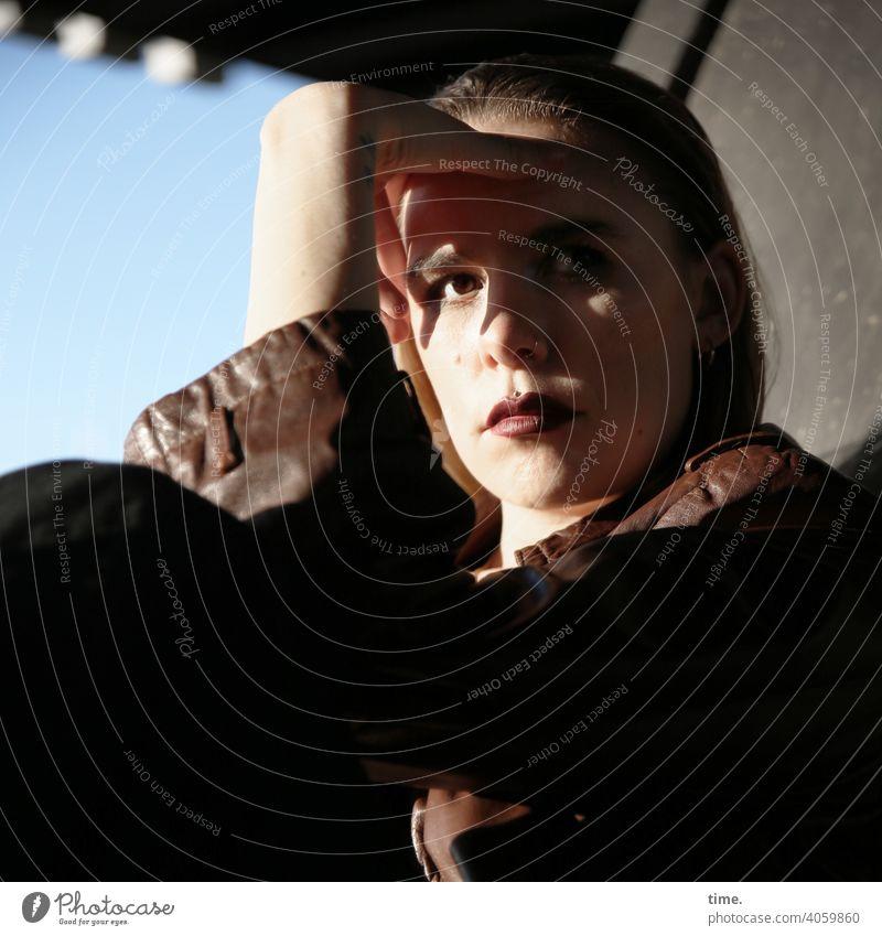 Lara skeptisch geheimnisvoll urban schatten sonnig brückenpfeiler metall ledermantel Haare blond blick Frau seitenlicht hand aufstützen schauen beobachten