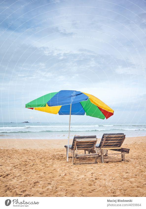 Sonnenschirm mit zwei Sonnenliegen an einem leeren tropischen Strand, Sri Lanka. Urlaub Regenschirm Flucht sich[Akk] entspannen friedlich Stuhl Liege Sonnenbank