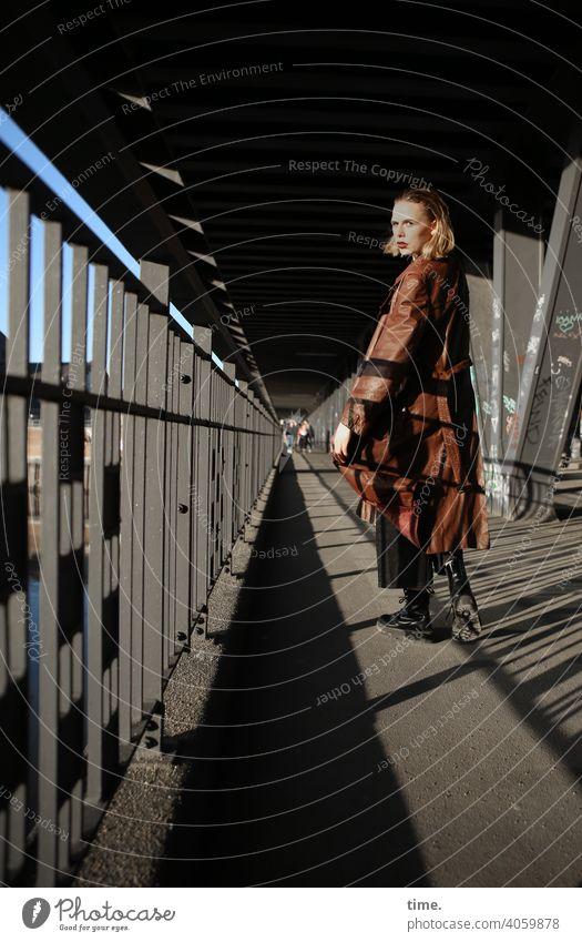 Lara skeptisch geheimnisvoll urban schatten sonnig brückenpfeiler metall ledermantel Haare blond blick Frau gehen umschauen
