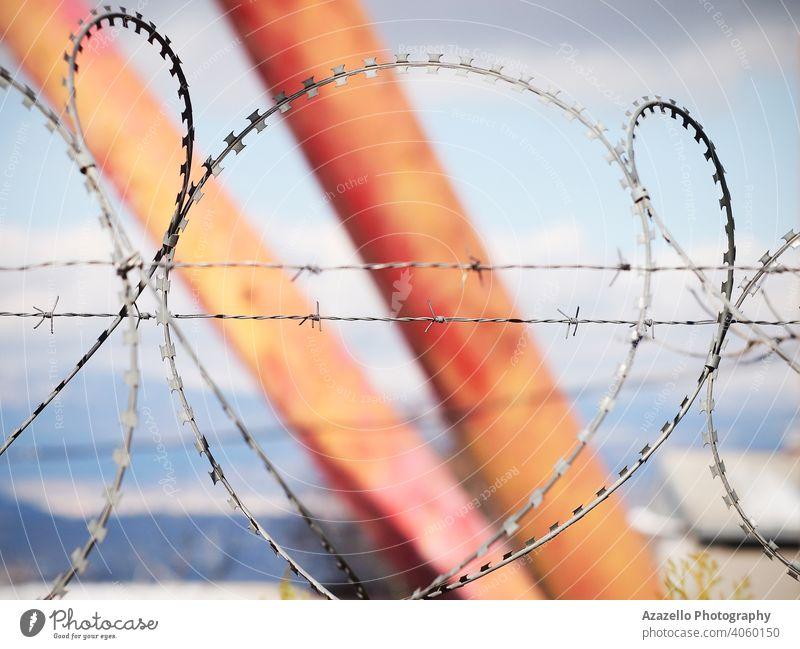 Stacheldraht über den Zaun auf einem unscharfen Hintergrund mit Stacheln versehen blau verschwommen Bokeh Hintergrund Borte Begrenzung Konzept Gefahr Eingang