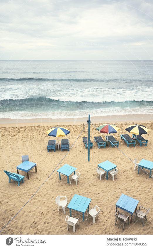 Luftaufnahme eines leeren tropischen Strandes mit Sonnenschirmen, Sonnenliegen, Tischen und Stühlen, Farbabtönung aufgetragen, Sri Lanka. Antenne Resort Urlaub