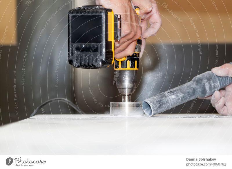 Handwerker schneiden runde Löcher für Steckdosen in Marmor-Arbeitsplatte für die Küche mit Handbohrer Aktion Vorrichtung Klinge kreisen Raumpfleger Nahaufnahme