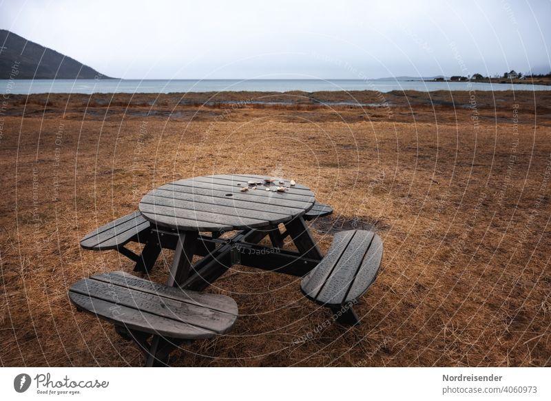 Rastplatz am Meer im Regen strand regen meer campingplatz sitzbank küste rastplatz atlantik nordatlantik wasser wiese gras fjord senja insel norwegen strandgut