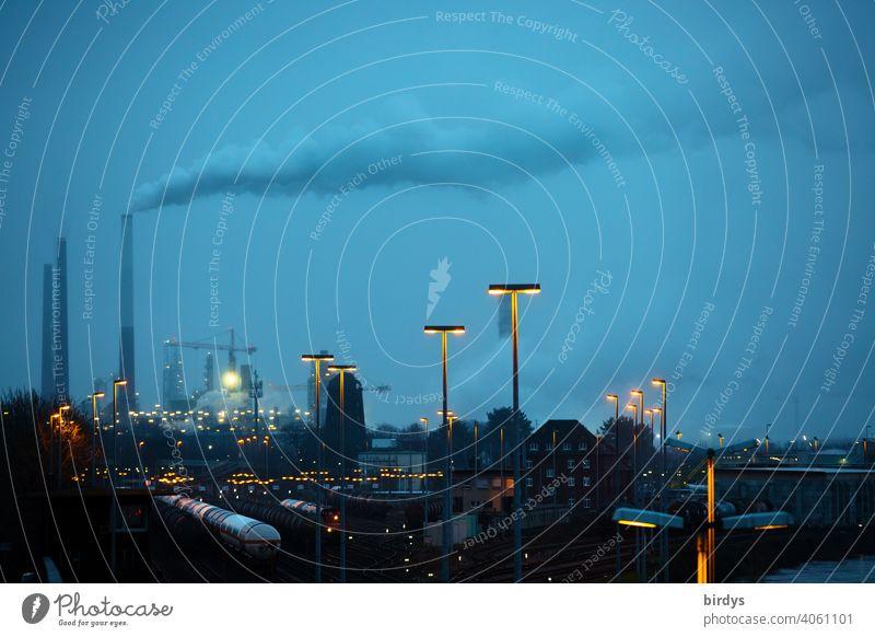 Industrielandschaft zur blauen Stunde. Rauchende Industrieschlote , Güterzüge auf Gleisanlagen und viele Lichter Indusrtrie Chemieindustrie CO2