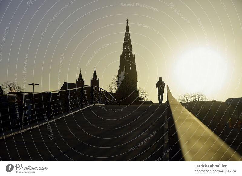 Strahlkraft freiburger münster frühling silhouette glaube einsam hoffnung religiösität aufblühen erleichterung mensch mann schatten kirche abendrot weg brücke