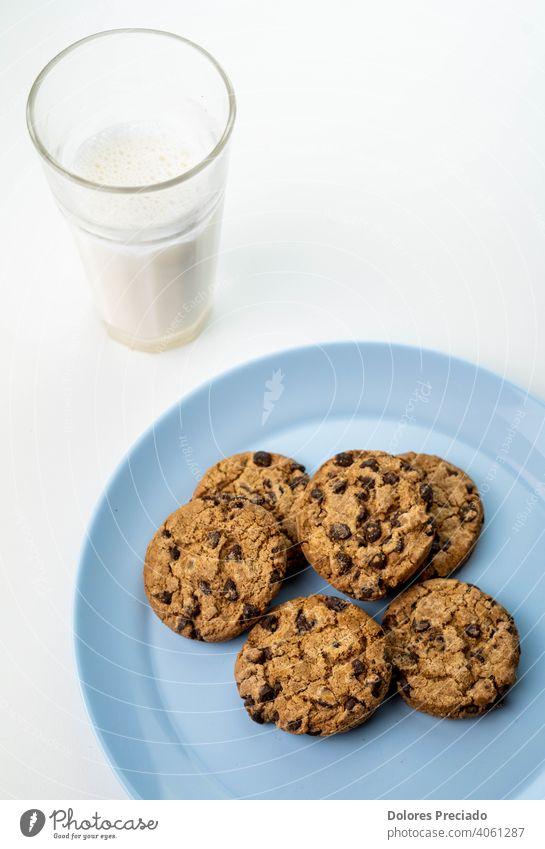 Teller mit Schokoladenkeksen und ein Glas Milch Frühstück melken natürlich Keks Chip trinken süß Lebensmittel Biskuit Farbfoto Mahlzeit hölzern heimisch Gebäck