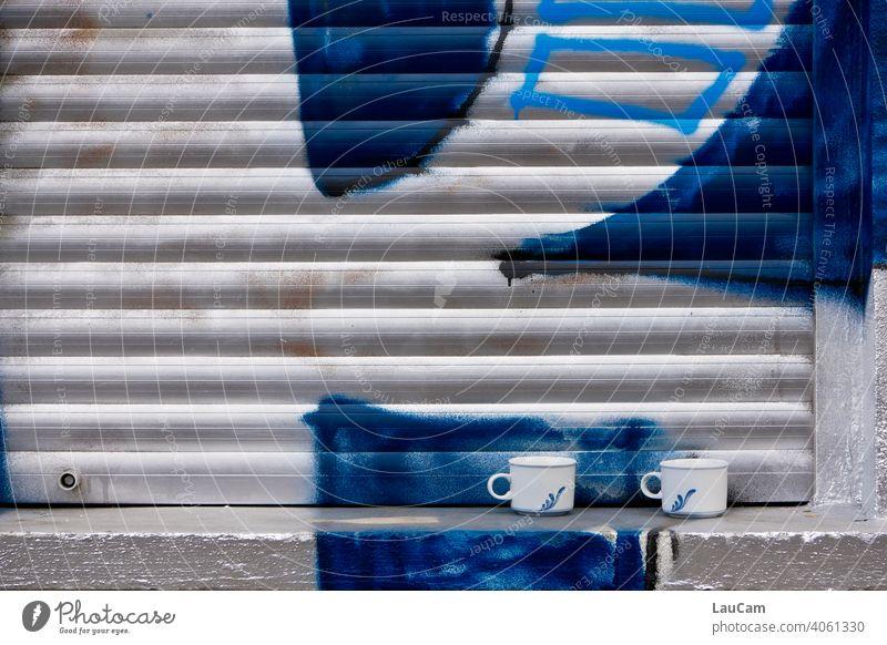 Zwei Tassen auf einer Fensterbank vor geschlossenem Rolladen mit silber-blauem Graffiti Rollladen Rollo weiß silbern Kaffee Kaffeetasse Kaffeetassen
