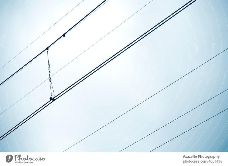 Traktionsdrähte Ansicht gegen den Himmel. Minimalistisches Bild von diagonalen Drähten. abstrakt Hintergrund schwarz blau Business Kabel aktuell Gefahr Design