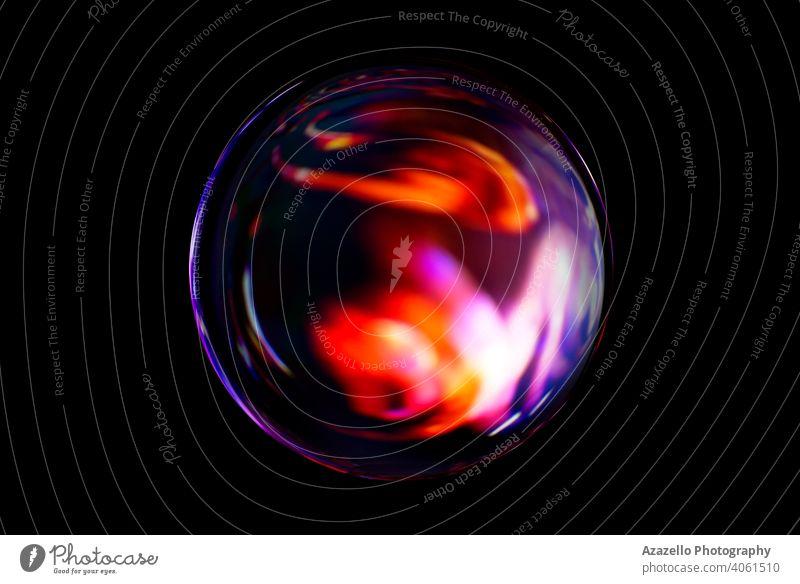Unscharfes Bild einer glänzenden Kristallkugel mit abstrakten verschwommenen bunten Muster. Abstrakte Linsenkugel in Unschärfe. 3d Hintergrund Ball Strahl
