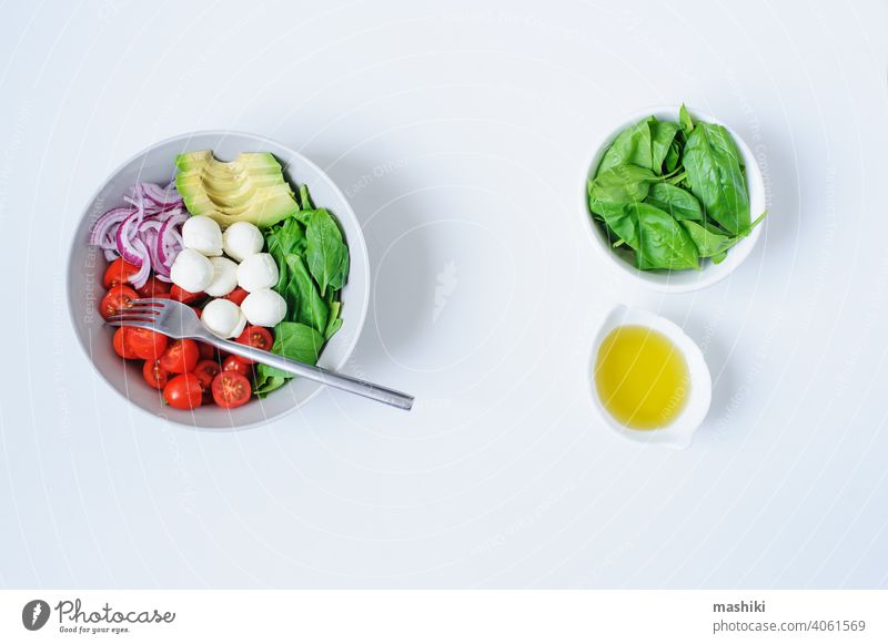 Frühstücks-Gesundheitsdiät-Bowl mit Kirschtomaten, Avocado, Blattspinat, Mozzarella und roten Zwiebeln mit Olivenöl-Dressing Tomate Gemüse Salatbeilage