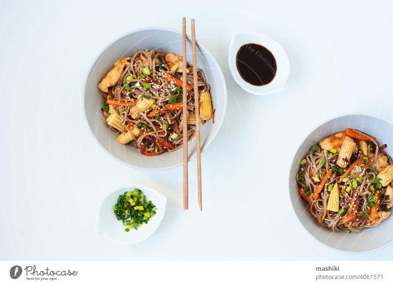 Japanisches Gericht Buchweizen-Soba-Nudeln mit Huhn und Gemüse Karotte, Zwiebel und Babymais soba Lebensmittel Essstäbchen Schalen & Schüsseln Mahlzeit