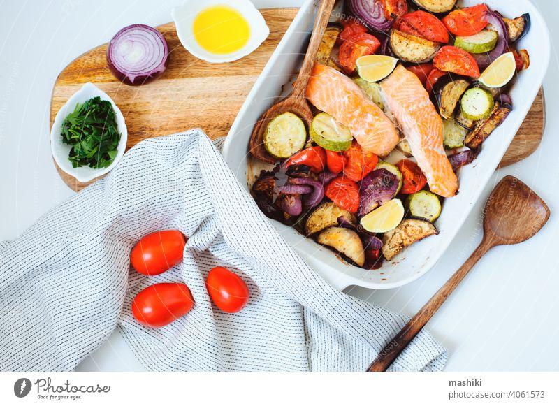 Ofengeröstete Gemüsemischung - Tomate, rote Zwiebel, Zucchini und Aubergine mit gebackenem Lachs. Gesunde Diät vegetarisches Abendessen oder Mittagessen