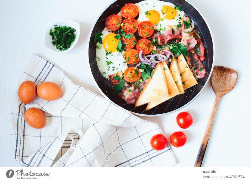 leckeres Komfort-Frühstück in der Pfanne serviert - Spiegeleier, Kirschtomaten, Speck, rote Zwiebeln und getoastetes Brot. Ei Tomate Lebensmittel Mahlzeit