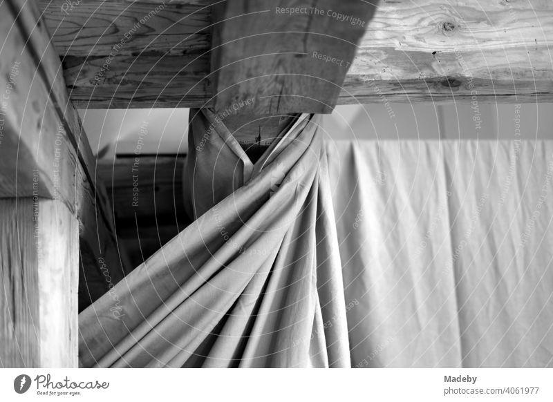 Schöne alte Dachbalken aus Holz unter dem Dach und Vorhang mit Falten in einem renovierten Bauernhaus auf einem Bauernhof in Rudersau bei Rottenbuch im Kreis Weilheim-Schongau in Oberbayern, fotografiert in klassischem Schwarzweiß