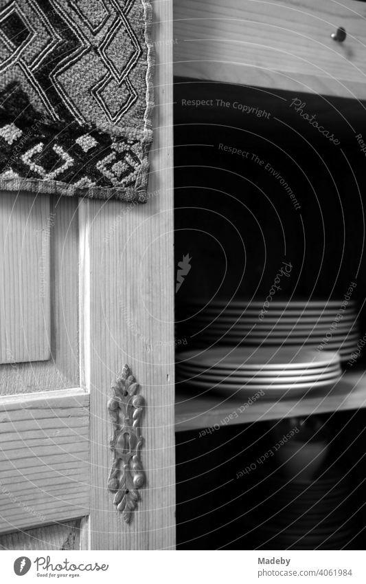Weiße Teller auf dem Regalboden eines alten Bauernschrank aus massivem Holz im Wohnzimmer eines alten Bauernhaus in Rudersau bei Rottenbuch im Kreis Weilheim-Schongau in Oberbayern, fotografiert in neorealistischem Schwarzweiß