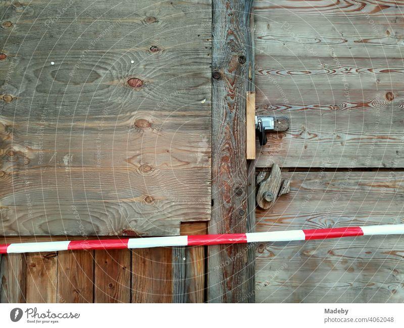 Rotweißes Absperrband vor einer Holzhütte mit Holztür aus rustikalem Holz mit Vorhängeschloss vor Beginn des Weihnachtsmarktes in der Hansestadt Lemgo bei Detmold in Ostwestfalen-Lippe