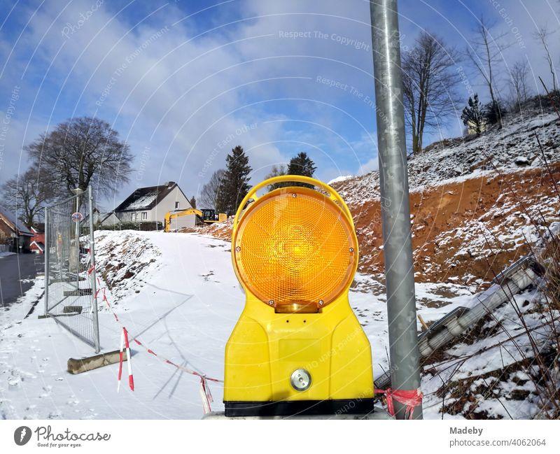 Gelb leuchtende Warnleuchte im Winter mit Schnee und Sonnenschein an einer Baustelle in Oerlinghausen bei Bielefeld am Hermannsweg im Teutoburger Wald in Ostwestfalen-Lippe