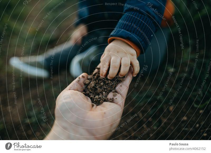 Kind pflückt Erde aus der Hand des Vaters Boden Kindheit Bildung Nahaufnahme erkunden authentisch Farbfoto Fröhlichkeit Kaukasier Freude Lifestyle Tag Spielen
