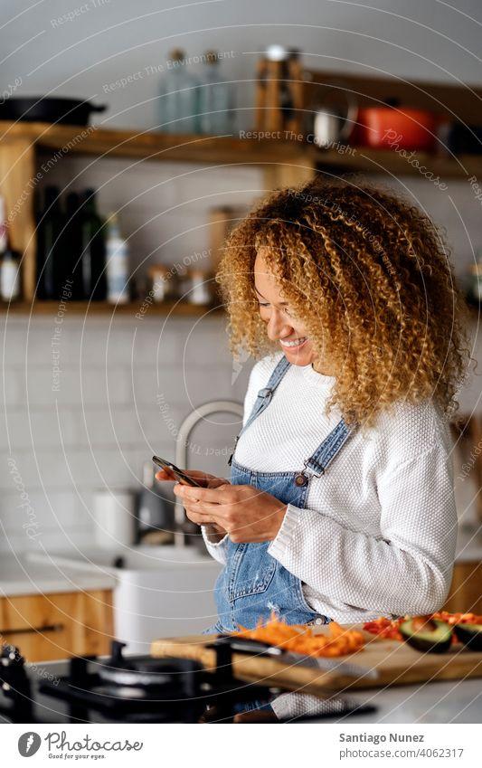 Frau schreibt eine SMS mit ihrem Smartphone. Lebensmitte Paar Liebe Essen zubereiten heimwärts gemütlich Kaukasier Partnerschaft vorbereitend Glück Person Herd